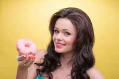 Sexy woman with sweets. Sexy dark-haired smiling woman wearing pretty mint dotted dress holding tasty doughnut in her hand and demonstrating it to us. Isolated Royalty Free Stock Photos