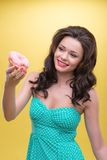 Sexy woman with sweets. Sexy dark-haired smiling woman wearing pretty mint dotted dress holding tasty doughnut in her hand and wanted to bite off the piece Stock Photography