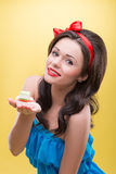 Sexy woman with sweets. Half-length portrait of charming smiling dark-haired woman wearing nice red headband and wonderful blue dress holding on her palm very Stock Photo