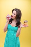 Sexy woman with sweets. Half-length portrait of sexy dark-haired woman holding in one hand three doughnuts and trying to bite pound cake in another. Isolated on Stock Images