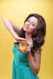 Sexy woman with sweets. Half-length portrait of sexy dark-haired woman wearing nice mint dotted dress holding in hands very appetizing round sweet doughnut Stock Image