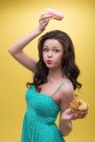 Sexy woman with sweets. Half-length portrait of funny dark-haired woman with bloated cheeks wearing nice mint dotted dress holding one doughnut over her head and Royalty Free Stock Photos