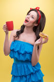 Sexy woman with sweets. Half-length portrait of lovely dark-haired woman holding tasty doughnut in one hand and aromatic coffee in another and dreaming about her Stock Image