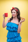 Sexy woman with sweets. Half-length portrait of lovely dark-haired woman holding tasty doughnut in one hand and aromatic coffee in another and dreaming about her Stock Images