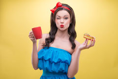 Sexy woman with sweets. Half-length portrait of lovely dark-haired woman wearing nice red headband and wonderful blue dress kissed us holding tasty doughnut in Royalty Free Stock Photos