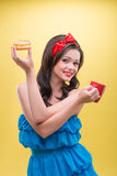 Sexy woman with sweets. Half-length portrait of lovely smiling dark-haired woman embracing herself holding in both hands iced doughnut and hot coffee. Isolated Royalty Free Stock Photo