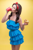 Sexy woman with sweets. Half-length portrait of lovely smiling dark-haired woman wearing nice red headband and wonderful blue dress standing aside to us drinking Royalty Free Stock Photo