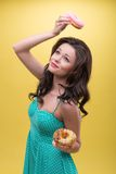 Sexy woman with sweets. Half-length portrait of pretty dreaming dark-haired woman wearing nice mint dotted dress holding one doughnut over her head and another Royalty Free Stock Photo