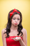 Sexy woman with sweets. Half-length portrait of sad slovenly dark-haired girl wearing great red headband holding one little piece of her favorite dessert on her Stock Images