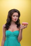 Sexy woman with sweets. Half-length portrait of very nice dark-haired woman wearing pretty mint dotted dress holding tasty doughnut in her hand and thinking how Royalty Free Stock Image