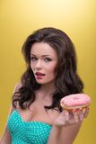 Sexy woman with sweets. Half-length portrait of very nice dark-haired woman wearing pretty mint dotted dress holding tasty doughnut in her hand and thinking how Royalty Free Stock Photos
