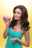 Sexy woman with sweets. Half-length portrait of very nice smiling dark-haired woman wearing pretty mint dotted dress holding tasty doughnut in her hand and Stock Photography