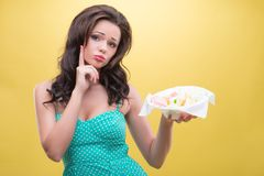 Sexy woman with sweets. Half-length portrait of very pretty thoughtful dark-haired girl holding in one hand a little basket with colorful fruit drops. Isolated Royalty Free Stock Image