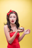 Sexy woman with sweets. Half-length portrait of very surprised dark-haired woman wearing great red headband holding tasty chocolate cake and looking at us Stock Images