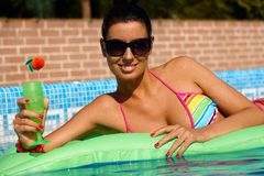 Sexy woman in swimming pool in bikini smiling Stock Photography