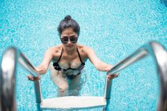 Sexy woman at swimming pool ladder. Beautiful Asian tan sexy woman in a black bikini and sunglasses walks out of swimming pool through a ladder. Summer concept Stock Photos