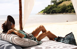 Sexy woman in swimsuit and hat relaxing on beach of Phuket Stock Images