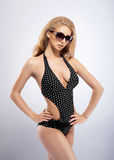 A sexy woman in a swimsuit posing in sunglasses Stock Photography
