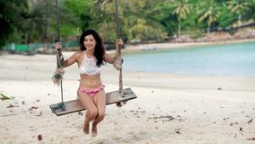 Sexy woman swinging at tropical beach swing stock footage