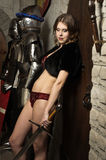 Sexy woman with a sword in a medieval castle interior Stock Images