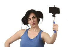 woman taking selfie photo with stick and mobile phone camera posing happy Stock Image