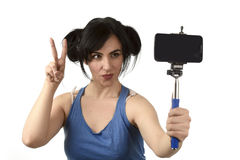 woman taking selfie photo with stick and mobile phone camera posing happy Stock Images