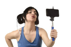 Sexy woman taking selfie photo with stick and mobile phone camera posing happy. Young attractive and sexy woman taking selfie photo with stick and mobile phone Royalty Free Stock Image