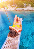Sexy woman tanning on sailboat. Female relaxing above transparent blue sea, girl enjoying bright sun light, active lifestyle, happy summer vacation Stock Image