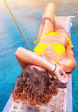 Sexy woman tanning on sailboat. Female relaxing above transparent blue sea, girl enjoying bright sun light, active lifestyle, happy summer vacation Royalty Free Stock Image