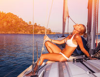 Woman tanning on yacht. Enjoying warm sunlight, seductive model wearing white stylish swimwear and posing on deck of sailboat in sunset light, summer holidays stock images