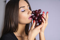 Sexy woman tasting red grapes Royalty Free Stock Photos