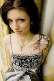 Sexy woman with tattoo in dress. Tattooed woman - sexy brunette prom queen in silver dress Royalty Free Stock Photos