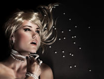 Sexy woman with torn beads. Fashion portrait of beautiful seductive woman ripped her luxury pearl beads, closeup on face with perfect stylish makeup, blond sexy Stock Images