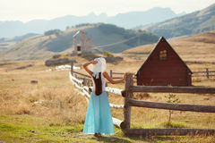 Sexy woman travel countryside alone. Wooden houses and mountains background Stock Images
