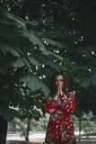 Woman under the chestnut. girl dressed in red jumpsuit in tropical ornament.model ip posing. Woman under the chestnut royalty free stock photo