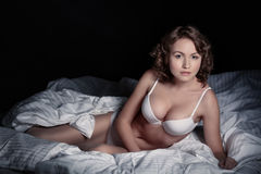 Sexy woman in underwear lying on a bed in a dark room. Royalty Free Stock Photos