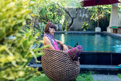 Sexy woman using laptop computer on a lounge near swimming pool outdoors. Tropical garden of Bali island, Indonesia. Stock Photography