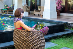 Sexy woman using laptop computer on a lounge near swimming pool outdoors. Tropical garden of Bali island, Indonesia. Sexy woman using laptop computer on a Stock Photography