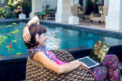 Sexy woman using laptop computer on a lounge near swimming pool outdoors. Tropical garden of Bali island, Indonesia. Stock Images
