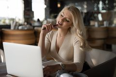 Sexy woman using laptop pc sitting in cafe. Sexy woman using and working by laptop pc sitting in cafe, attractive businesswoman royalty free stock image