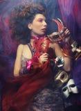 Sexy woman with venetian masks lay on organza Stock Photos