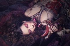 Sexy woman with venetian masks lay on organza Royalty Free Stock Image