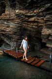 Sexy woman walking on wooden path at sea cave Stock Photos