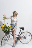 Sexy woman watering with bicycle Royalty Free Stock Photos