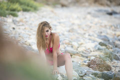 woman wear pink bikini sitting on sea rocks Stock Images