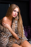 Woman wearing a fur coat posing Royalty Free Stock Photos