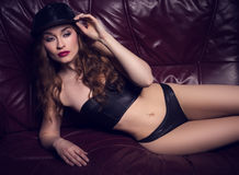 Sexy woman wearing leather lingerie and hat Stock Photography