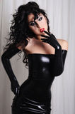 woman wearing long black latex gloves and a latex dress stock photography