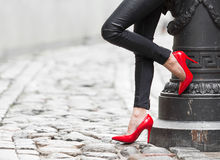 Sexy woman wearing red high heel shoes in city. Sexy woman wearing leather pants and red high heel shoes in city
