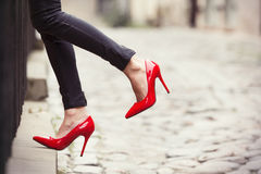 Woman wearing red high heel shoes in city. Woman wearing leather pants and red high heel shoes in city stock image